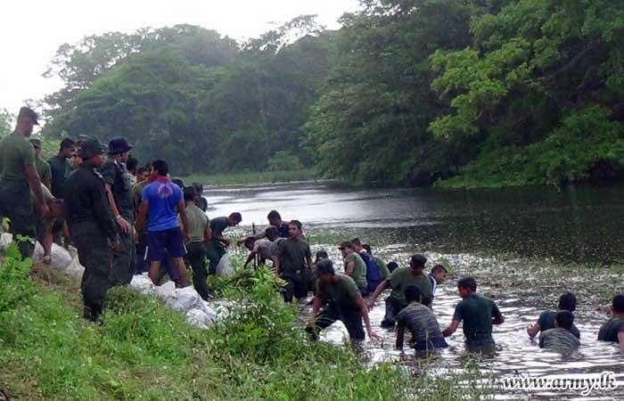 படையினர் மற்றும் உலியன்குலம் கிராம வாசிகள் இணைந்து 2800 மணல் மூட்டைகள் பயன்படுத்தி அணைக்கட்டு சீரமைக்கும் பணிகளில்